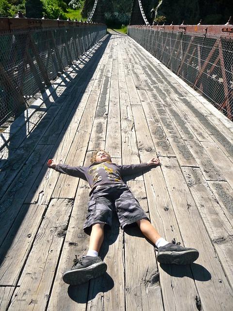 橋の上に寝る少年
