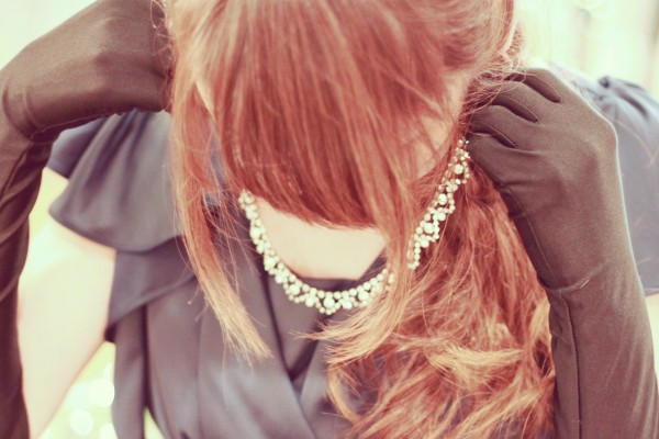 ネックレスをつける女性