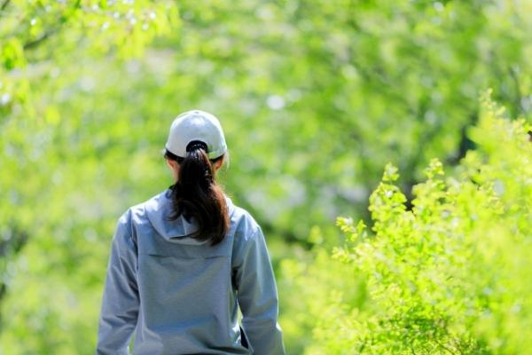 緑の中を歩く女性
