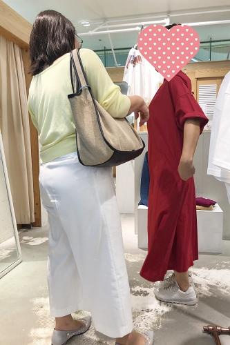 赤いワンピースを試着する女性