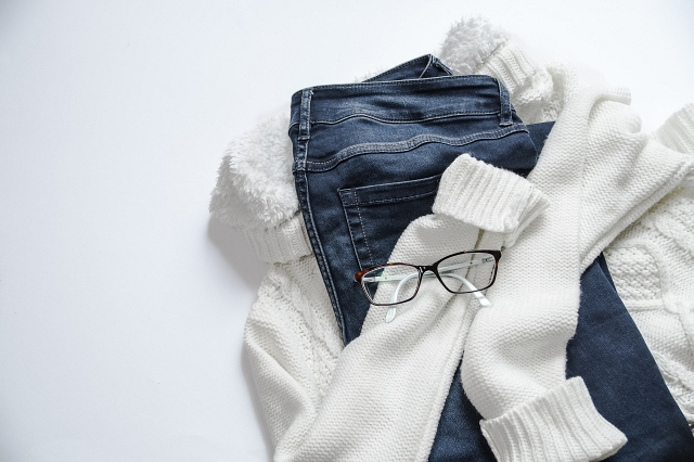 デニムと白いセーターの上にある黒いめがね