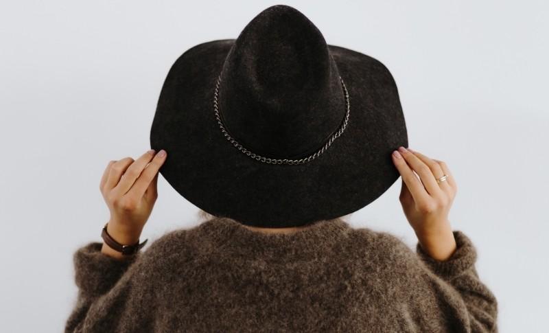 黒い帽子をかぶった茶色いセーターの女性