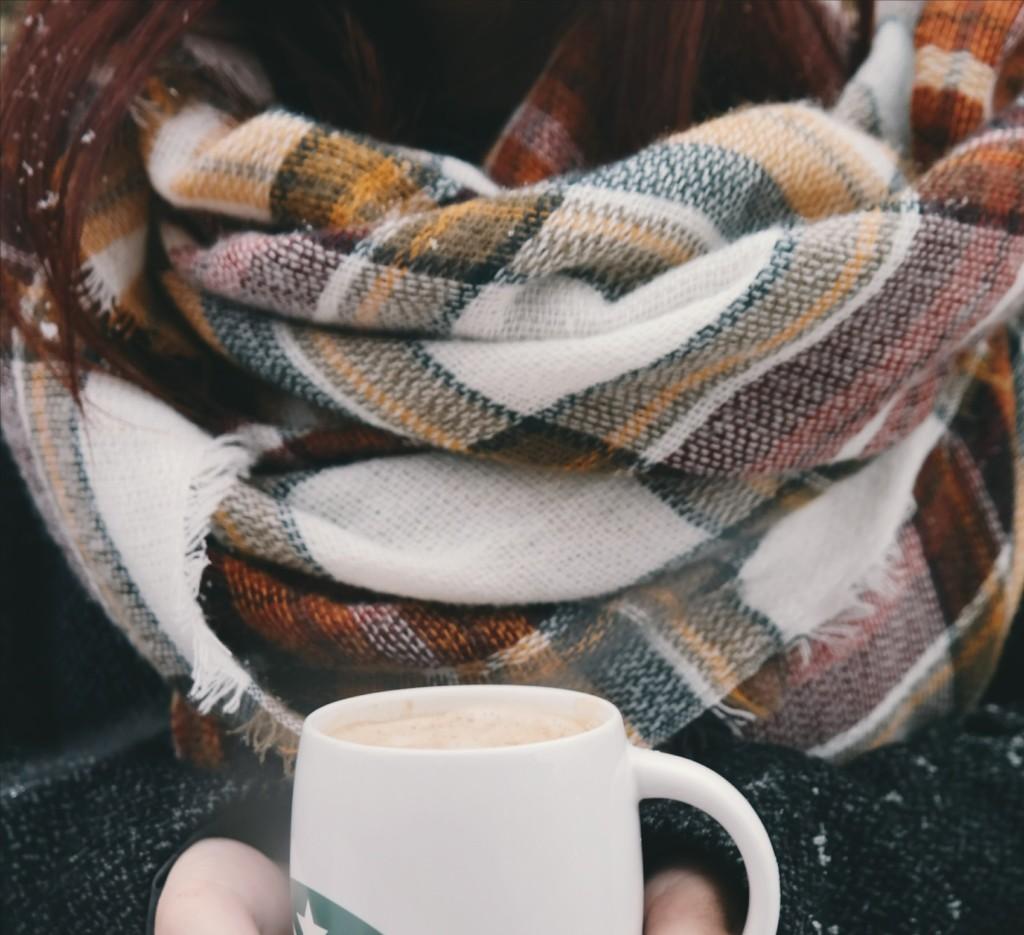 コーヒーカップを持つチェックのストールを巻いた女性