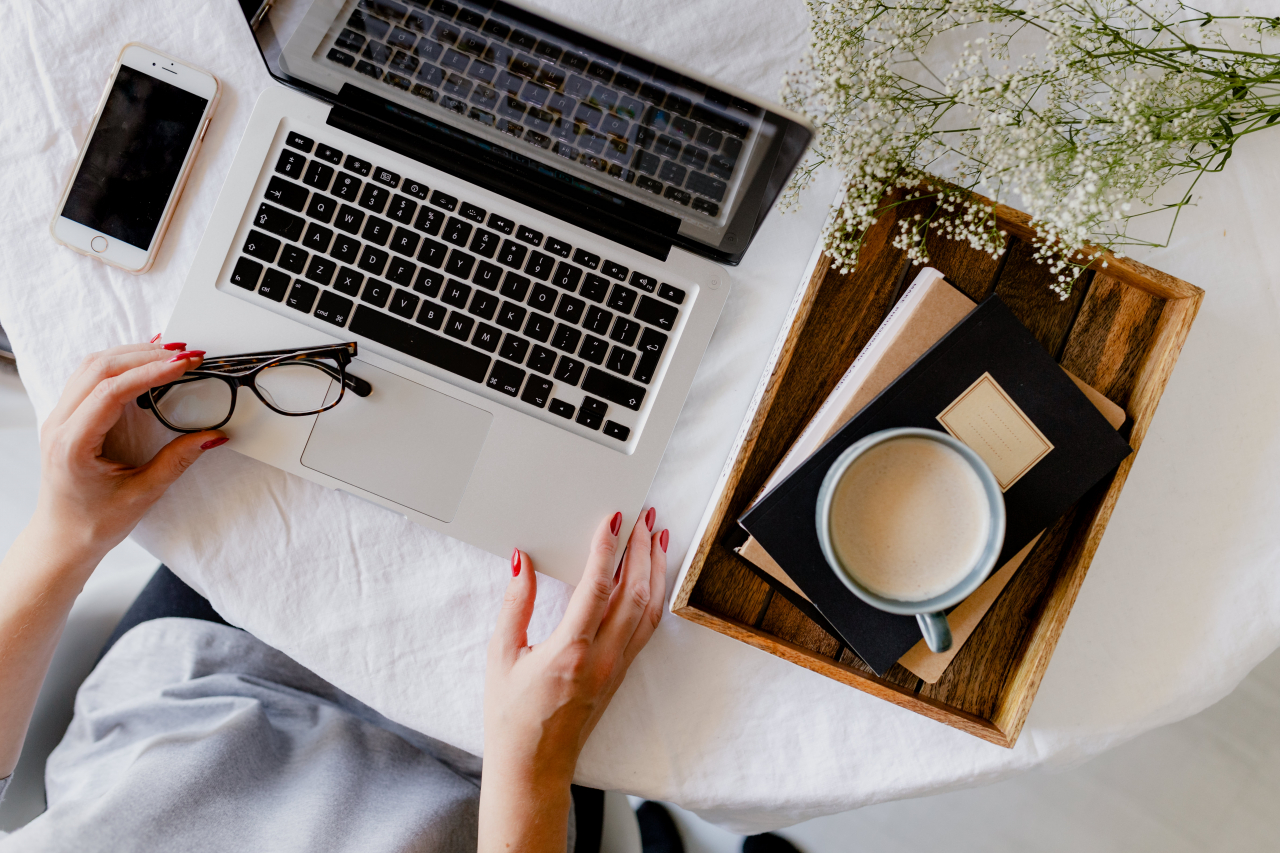 机の上でノートパソコンを使う女性の手
